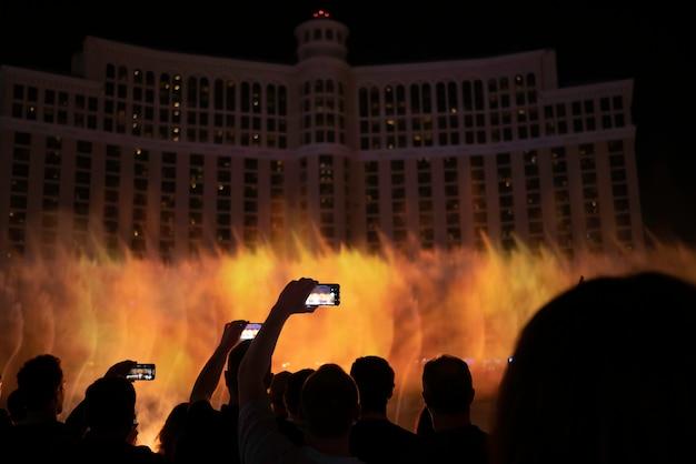 人々のシルエットグループは夜に有名な噴水の写真を撮る。