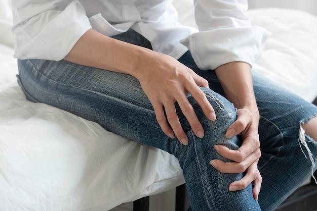 膝の痛みに苦しんでいるジーンズを着た若い女性。