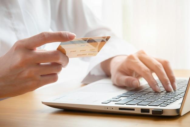 女性の手はテーブルの上のラップトップでクレジットカードを持ってオンラインで買う