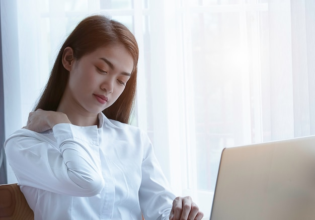 Синдром офиса с молодой азиатской болью плеча бизнес-леди, концепцией синдрома офиса.