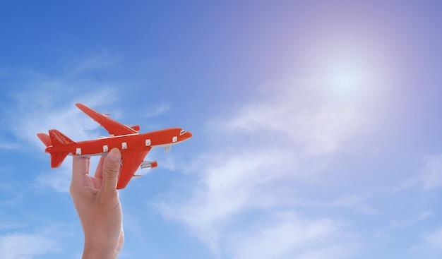 Закройте вверх руки женщины держа самолет игрушки на предпосылке голубого неба с солнечностью.