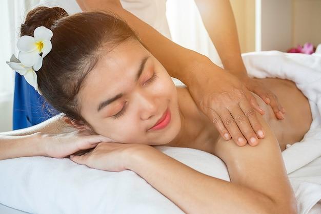 女性のソフトフォーカスは、スパサロンで女性の体にマッサージを手します。