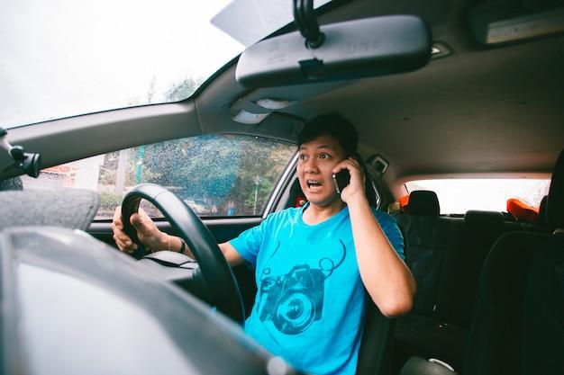 運転中の男性の電話機