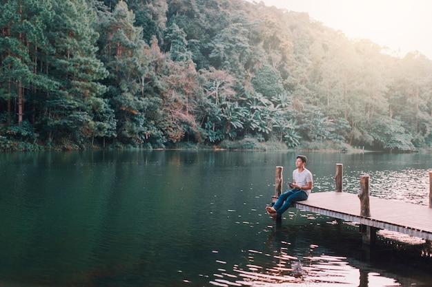 午後、湖畔の木製の橋で男性がリラックスしていた。
