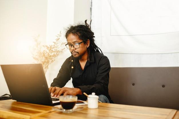 コーヒーショップに座ってラップトップで働く男