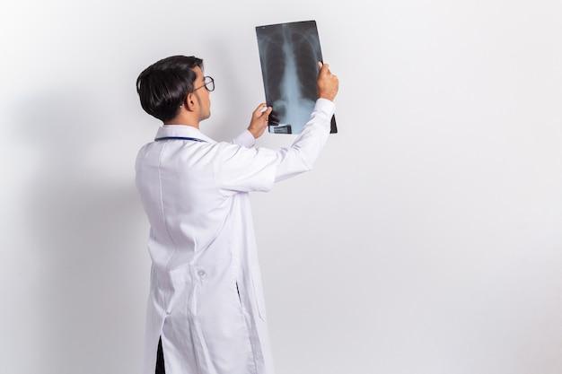 Доктор держит и смотрит рентгеновскую пленку