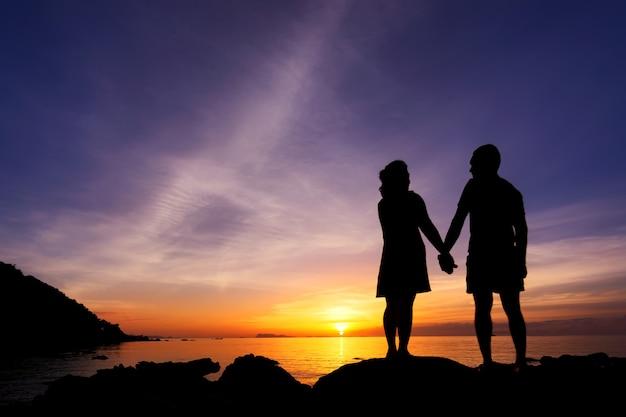 カップルのシルエットはビーチで自分の手を握る