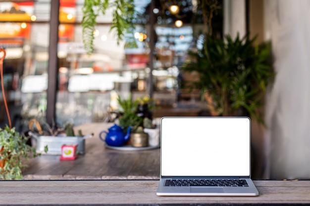 コーヒーショップの背景を持つテーブル上のラップトップ