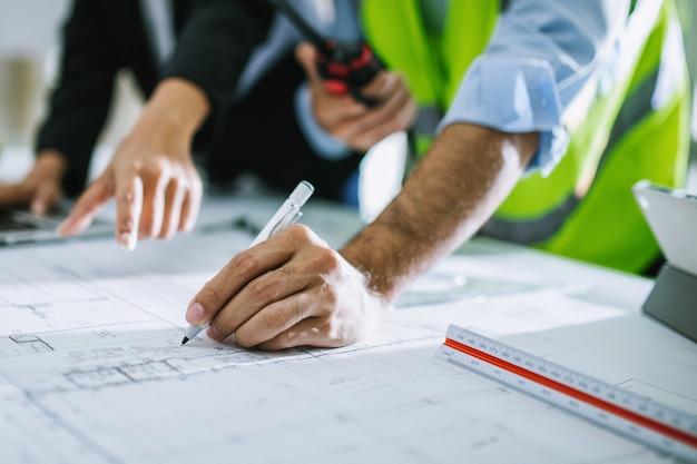 グラフィックを描く若い男性と女性の建築家の同僚