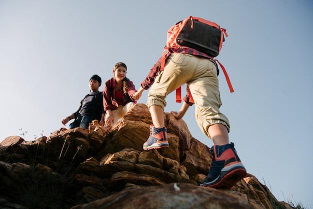 アジアのハイキングのグループは、日光の山でお互いのシルエットを助けます。