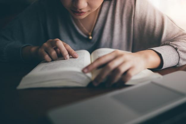 Молодой студент читая тайскую книгу на публичной библиотеке.
