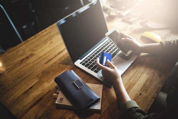 Молодая женщина держа кредитную карточку и используя портативный компьютер и умный телефон.