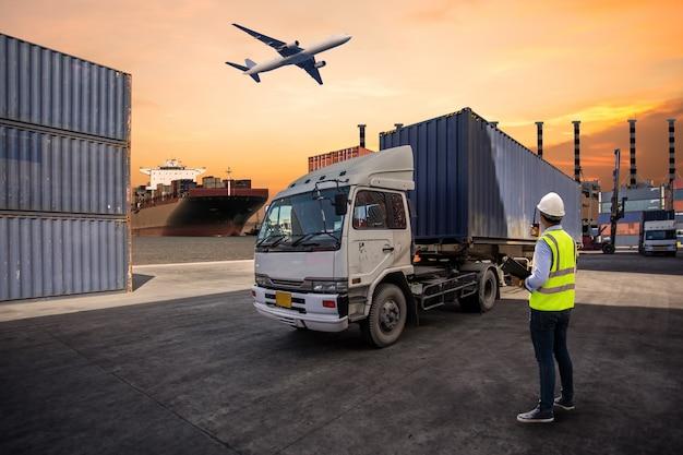 Бригадир контролирует погрузку контейнеров с коробки на грузовик