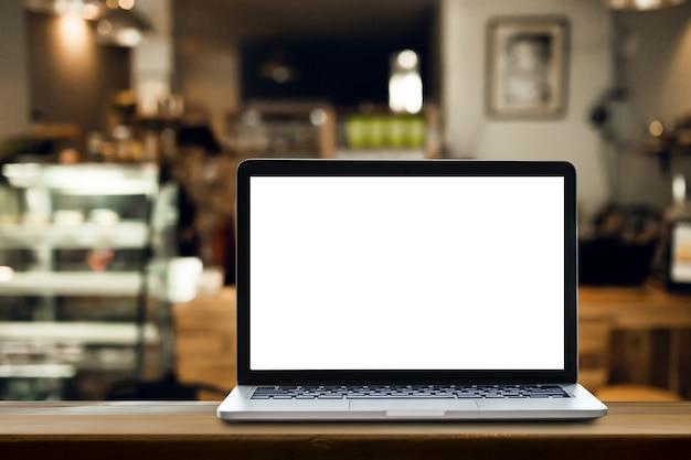 コーヒーショップの背景を持つテーブル上のラップトップ。