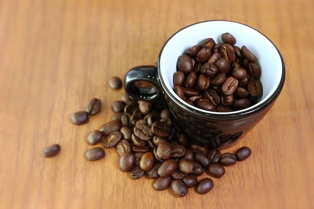 木製の背景にセラミックエスプレッソカップの黒い焙煎コーヒー豆のクローズアップイメージ