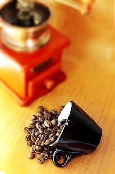 セラミックエスプレッソカップとヴィンテージスタイルグラインダーの木製の背中にあるダークローストコーヒー豆