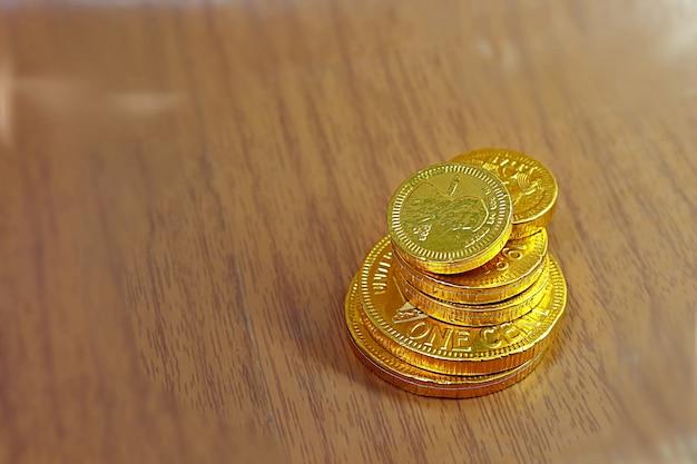 木製の背景に多くのサイズの金貨のクローズアップイメージ