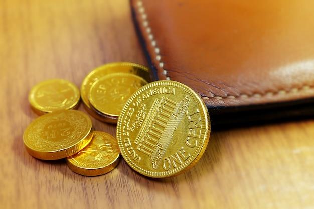 木製の背景に革ポケットマネーと多くのサイズの金貨のクローズアップイメージ