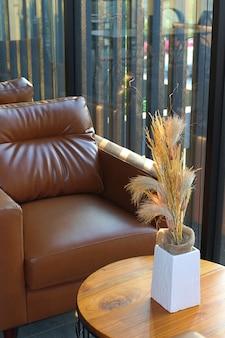 モダンなインテリアの木製テーブルを備えたブラウンレザーソファ。