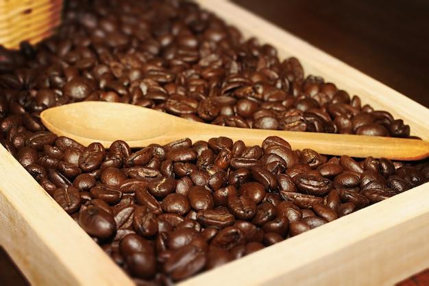 広告のために、木製のスプーンで木製トレイに黒い焙煎コーヒー豆。