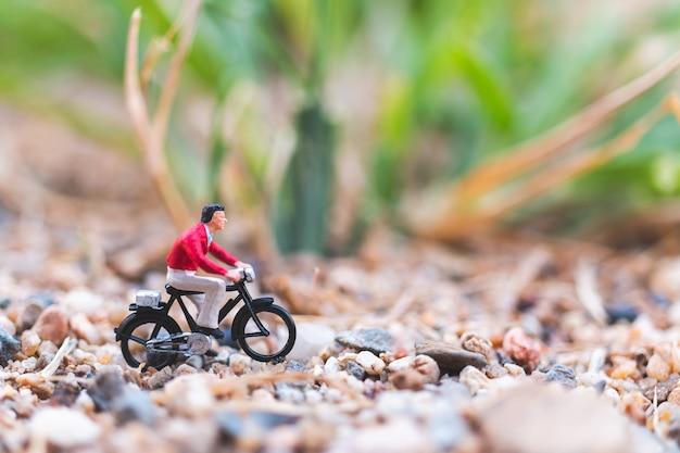 ミニチュアの人々:砂の上の自転車に乗る旅行者