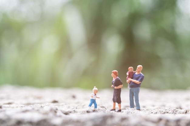 ミニチュアの人々:屋外を歩く子供を持つ親