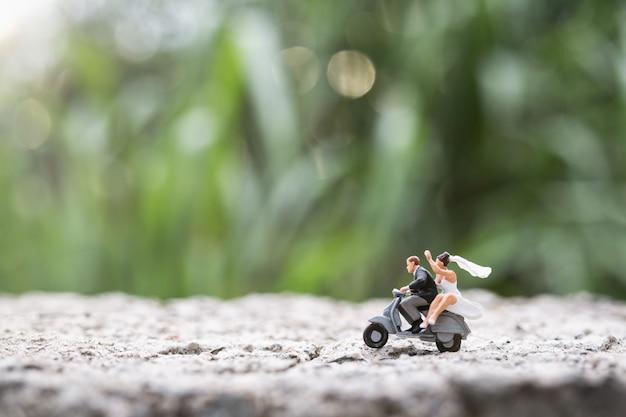 ミニチュアの人々:オートバイに乗るカップル