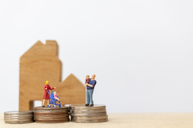 ミニチュアの人々:家とコインスタッキングを持つ子供を持つ親