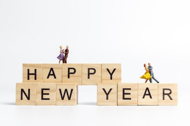 木製のブロックをレタリング幸せな新年に踊るカップル