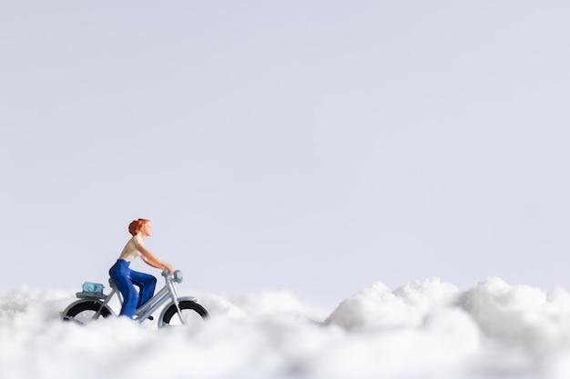 ミニチュアの人々:雪の上で自転車に乗る旅行者