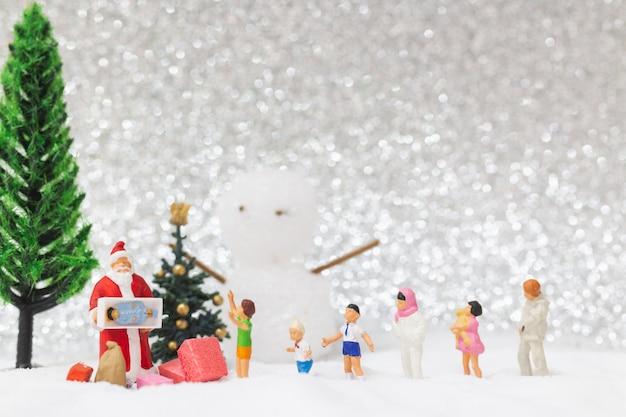 Миниатюрные люди: дед мороз и дети на снежном фоне