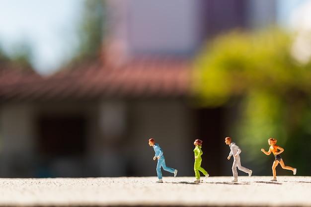 Миниатюрные люди: группа людей бежит по бетонной дороге