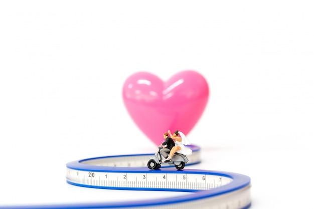 ミニチュアの人々:バイクに乗る愛のカップル