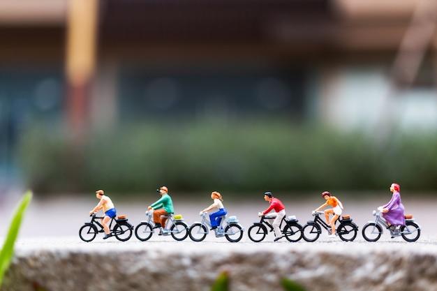 公園で自転車を持つミニチュアの人々旅行者