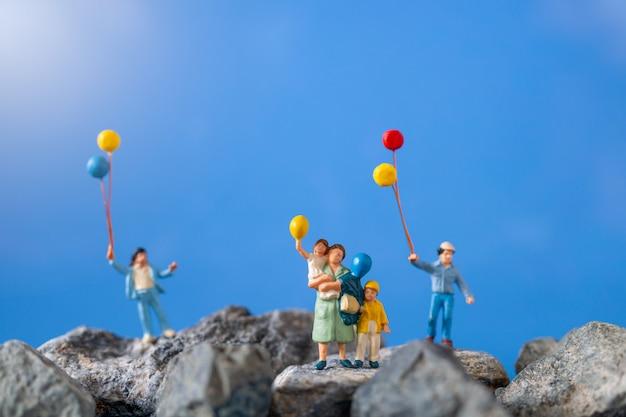 ミニチュアの人々、青い空と岩の上にバルーンを保持している幸せな家族