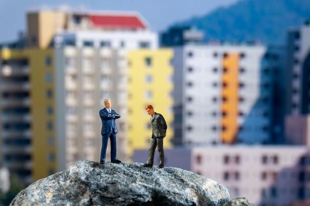 ミニチュアの人々、建物と岩の上に立っているビジネスマン