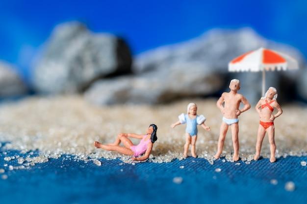 Миниатюрные люди в купальниках отдыхают на пляже