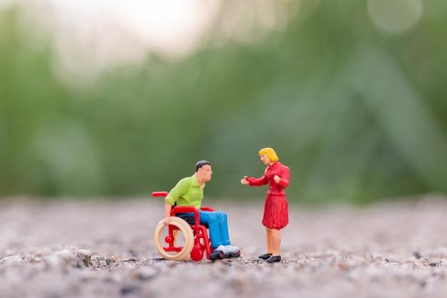 ミニチュアの人々:公園の車椅子に座っている障害者の男性とテキストのコピースペース