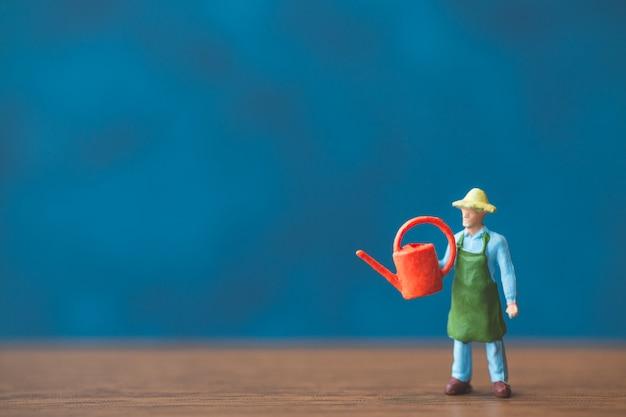 青い壁の背景の前に立っているミニチュア人庭師