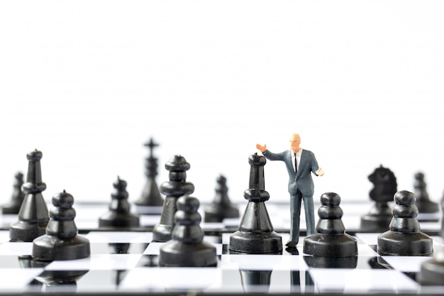 ミニチュアの人々チェス盤の上に立っての実業家