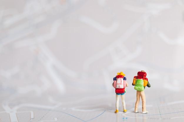Миниатюрные люди: путешественник с рюкзаком, идущий по карте