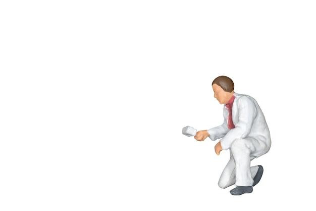 ミニチュアの人々:白い背景に描かれたブラシを持つ画家