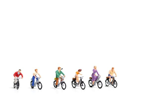 ミニチュアの人々:友人グループの自転車は、白い背景に分離