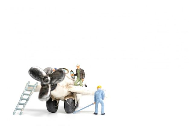 白い背景の上のおもちゃの飛行機を修理する労働者チーム