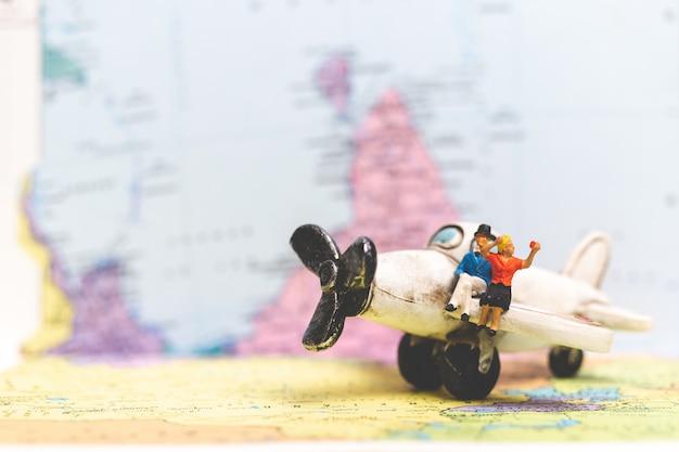 Миниатюрные люди, сидящие на самолете с фоном карты мира