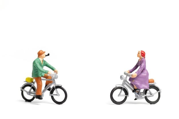 ミニチュアの人々:カップルは白い背景の上の自転車に乗る