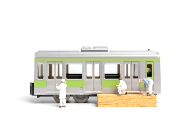白い背景の上に電車を塗る画家