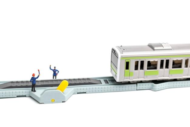 鉄道スタッフは白い背景の上の鉄道で働いています。