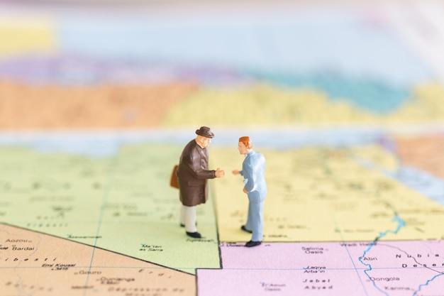世界地図背景に観光ハンドシェイク