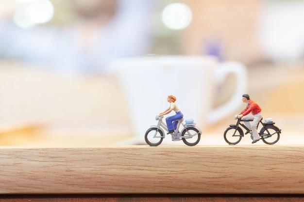 ミニチュアの人々が木の橋でサイクリング